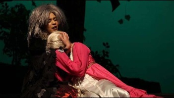 Rapunzel in the arms of the witch, played by Izzy Archer