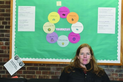 Maura Weir stands in front of campus wellness board. photo by Bruce McDaniel/MainSheet